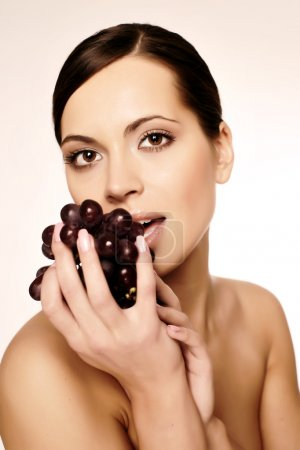 Beautiful young woman with grape