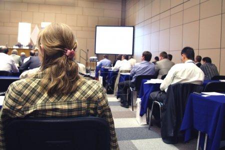 Photo pour Réunion dans une salle de conférence. mise au point est sous les cheveux de la Dame dans la partie gauche de l'image - image libre de droit