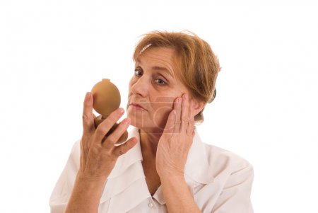 Elderly woman looks in the mirror