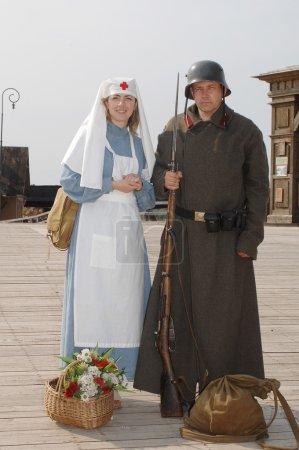 Photo pour Photo de style ancien avec femme en costume d'infirmière et homme en uniforme de soldat avec arme. Les costumes sont authentiques à ceux portés à l'époque de la Première Guerre mondiale . - image libre de droit