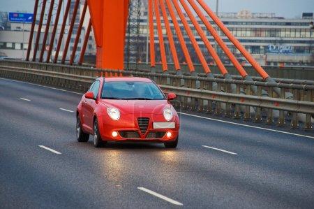 Photo pour Voiture rouge dans la ville sur câble pont, riga, Lettonie - image libre de droit