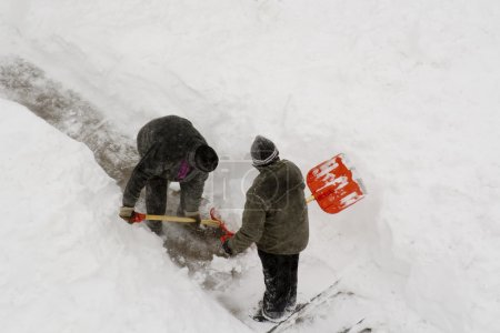2 worker cleaning deep snow