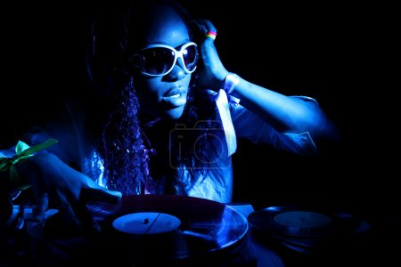 Foto de Cool dj afro americano en acción bajo luz azul - Imagen libre de derechos