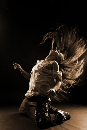 Photo for Cool woman modern dancer against black - Royalty Free Image