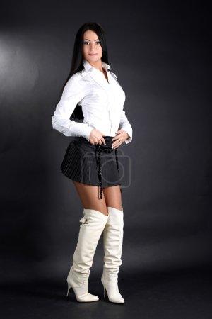 Photo pour Mode jeune femme en chemise blanche et bottes et jupe noire - image libre de droit