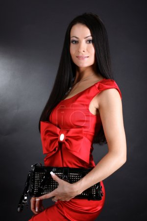 Woman in red dress with clutch bag