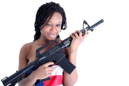 Photo pour Jeune femme afro-américaine dans le drapeau américain avec le fusil isolé sur blanc - image libre de droit