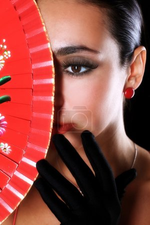 Latino woman with red fan