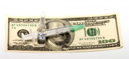 Photo for Syringe and ampoule with medicine on a banknote one hundred dollars. - Royalty Free Image