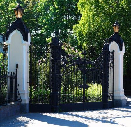 Photo pour Antiquités vieux fermé les deux lampadaire métal gateswith et deux colonnes blanches - image libre de droit