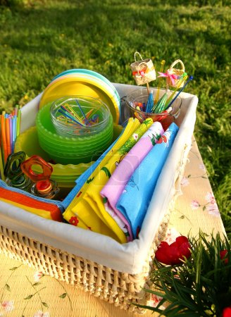 Foto de Una canasta con cosas en el césped, vertical y brillante verano multicolor picnic accesorios - Imagen libre de derechos