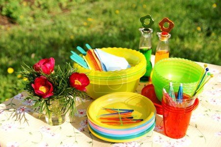 Foto de Una mesa con brillantes accesorios plásticos de picnic de verano multicolor, platos y platos, servilletas, botellas y flores - Imagen libre de derechos