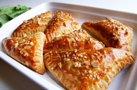 A white dish with baked puff-pastry pasties filled...