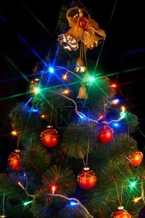 Foto de Árbol de Navidad con flash y campana. fondo negro. - Imagen libre de derechos