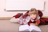jeune fille se trouvent près du radiateur avec livre