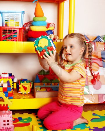 Child with puzzle and block in playroom