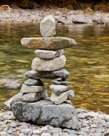 Photo pour Un inukshuk construit à partir de pierres se trouve à côté d'une rivière - image libre de droit