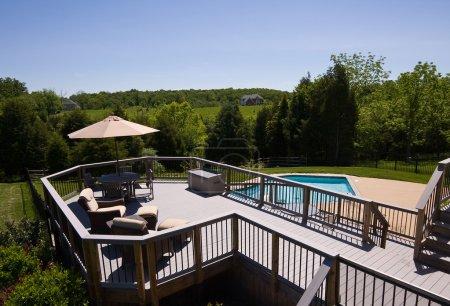 Photo pour Pont moderne en bois avec sièges et parasol donnant sur une piscine bleue - image libre de droit