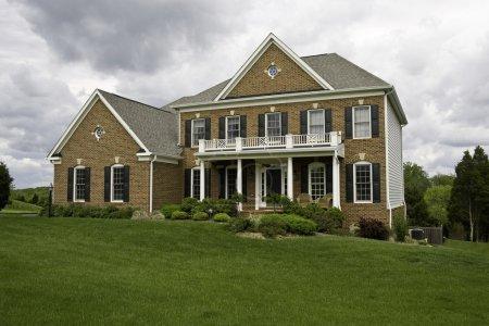 Photo pour Maison moderne avec pelouse paysagée et jardin par une journée lumineuse mais nuageuse - image libre de droit