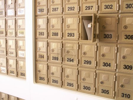 Photo for Letters in an open mailbox in a wall of mailboxes - Royalty Free Image