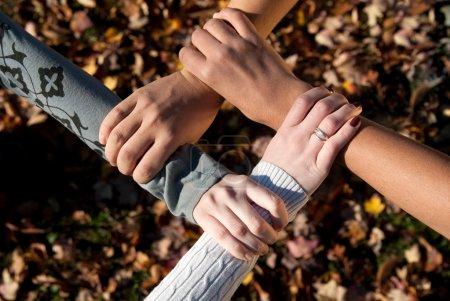 Photo pour Quatre adolescents de nationalités différentes se saisissent les poignets à l'extérieur à l'automne - image libre de droit