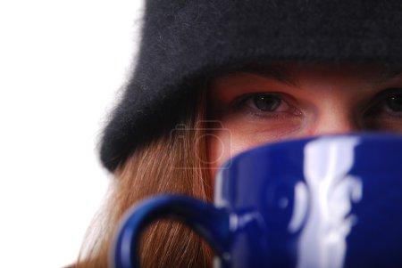 Mujer que mantiene caliente con taza de sopa o c