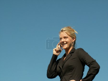 Photo for Business woman smiling at the news she is getting on her cell phone - Royalty Free Image