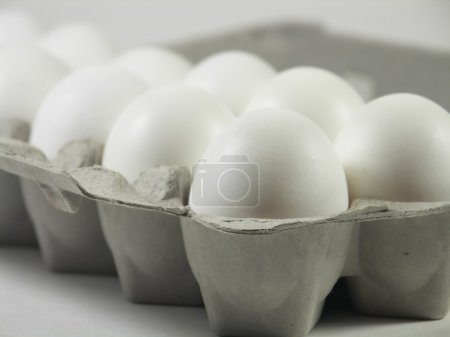 Photo for Carton of a dozen eggs with focus on front corner of carton - Royalty Free Image