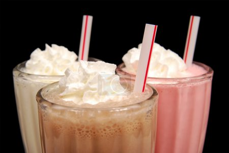 Photo for Three milkshakes with whipped cream against black - Royalty Free Image