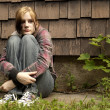 A teenage girl with a sad expression sits against ...