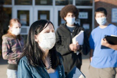 Photo pour Des élèves de diverses origines ethniques portant des masques devant une école. Focus sur la jeune fille devant . - image libre de droit