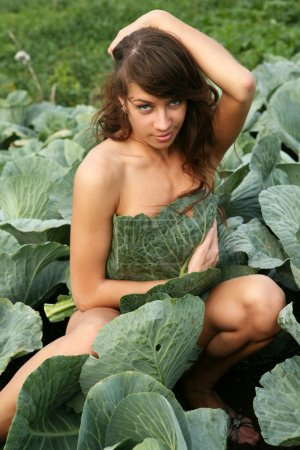 Photo for Young woman in brussels sprouts plant. - Royalty Free Image