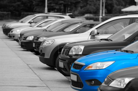 Photo for Black-and-white cars are on the parking and only one blue colored automobile. - Royalty Free Image