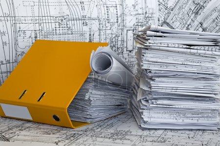 Photo pour Gros tas de dessins de conception et projet dans un dossier jaune sur la surface de la table. whatman blanc et noir sont fond. - image libre de droit