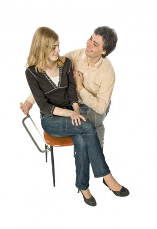 Photo for Man flirting with a woman sawing her chair leg - Royalty Free Image
