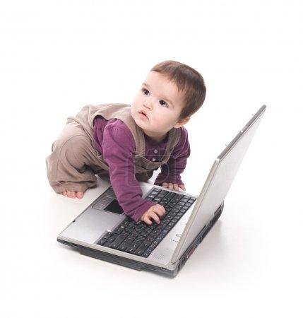 Photo pour Petite fille avec un ordinateur portable sur fond blanc - image libre de droit