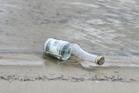 Photo for One hundred dollars note inside glass bottle lying in water on the river bank - Royalty Free Image