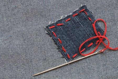 Photo for Needle and patch with red thread attached on jeans textured - Royalty Free Image