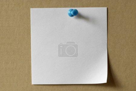 Photo pour Note autocollante blanche avec une broche bleue sur carton - image libre de droit