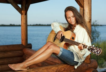 Photo for Young woman playing guitar in summerhouse on sunset - Royalty Free Image