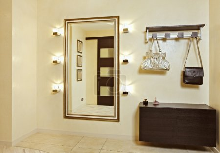 Hall in beige tones with hallstand and golden mirr...