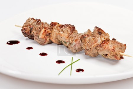 Pork kebab on white plate