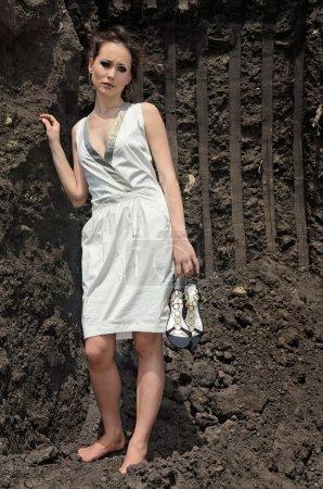 Photo pour Belle brune en robe de soleil blanche à l'intérieur d'une carrière de sol noir profond - image libre de droit
