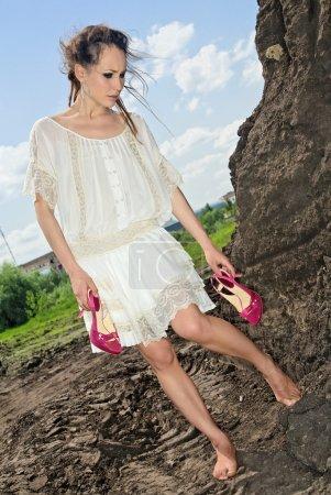 Photo pour Belle dame en blanc debout pieds nus avec des chaussures à talons rouges dans ses mains - image libre de droit