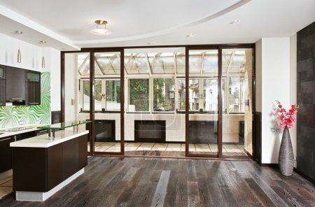 Foto de Moderna sala de dibujo (estudio) y cocina interior con balcón y suelo de madera oscura, vista frontal gran angular - Imagen libre de derechos