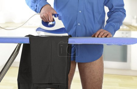 Photo for Man ironing his clothes at home, single lifestyle background - Royalty Free Image