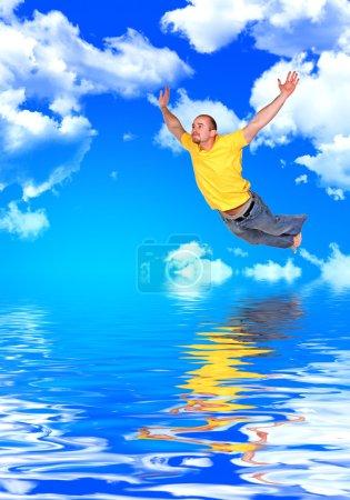 Photo pour Jeune homme sauter dans une métaphore de l'eau de la liberté - image libre de droit