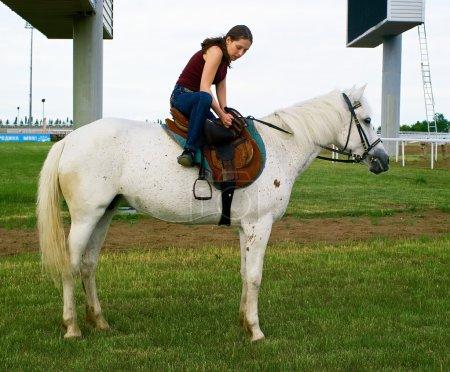 Girl astride a horse on a hippodrome