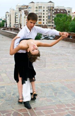 Photo pour Jeune couple danse latino danse contre le paysage urbain - image libre de droit