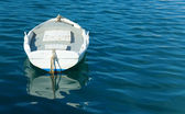 Single white boat and clear blue sea